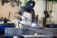 Free Handsome Man Workshop Welding Iron Spark Fire Hot Steel With A Power GMAW Welder And Protective Gear Stock Image - 187302371