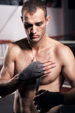Handsome man wrapping hand in boxing bandage Royalty Free Stock Image