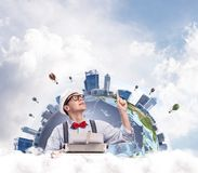 Creative inspiration of young writer. Handsome man writer in hat and eyeglasses pointing up while using typing machine at the table with Earth globe and cloudy Royalty Free Stock Photography