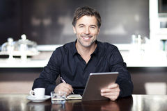Handsome Man Writing At The Coffee Shop. Stock Images