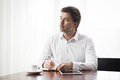 Handsome Man Writing At The Coffee Shop Royalty Free Stock Photos