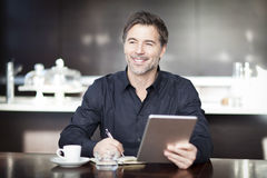 Handsome Man Writing At The Coffee Shop. Using Computer. Royalty Free Stock Images