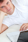 Handsome man writing on his laptop in his bedroom Stock Images