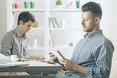 Handsome man writing in notepad. Portrait of handsome caucasian men in modern office writing in spiral notepad. Blurry colleague in the background. Young writer Stock Photo