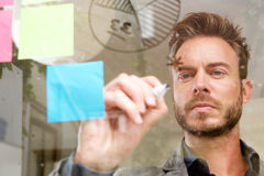Handsome man writing on transparent idea board thinking Stock Photos