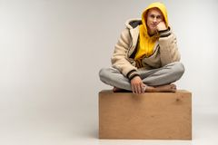 Handsome man in yellow hoodie sitting on wood cube royalty free stock images