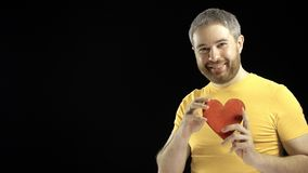 Handsome man in yellow tshirt holds red heart shape. Love, romance, dating, relationship concepts. Black background. 4K stock footage