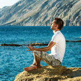 Handsome man in a yoga position on the beach Stock Photos