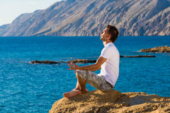Handsome man in a yoga position on the beach Royalty Free Stock Photos