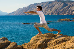 Handsome man in a yoga position on the beach Royalty Free Stock Images