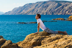 Handsome man in a yoga position on the beach Stock Image