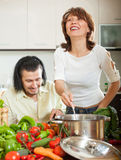 Handsome man and a young woman with vegetables in the kitchen Royalty Free Stock Images