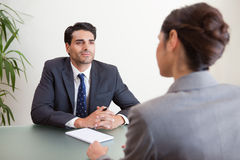 Handsome manager interviewing a female applicant Royalty Free Stock Photos