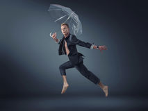 Handsome manager jumping with an umbrella Stock Photography