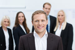 Handsome manager or team leader. Handsome friendly young manager or team leader with a confident smile posing in front of his team with shallow dof Stock Photos