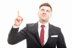 Handsome manager wearing suit pointing and looking up stock photography