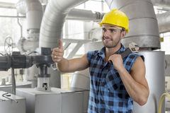 Handsome manual worker gesturing thumbs up in industry Stock Photos