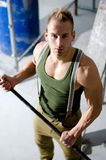 Handsome manual worker holding metal bar in his hands Royalty Free Stock Photography