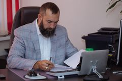 Handsome mature businessmen working with documents at office. Handsome mature bearded businessmen sitting at the table and working with documents at office Royalty Free Stock Image
