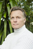 Handsome mature blond man in his forties. Wearing a white sweater and looking thoughtful Stock Photo