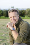 Handsome mature blond man in his forties. Smiling as he wears a green sweater and a brown wrist watch royalty free stock photo