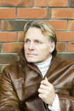 Handsome mature blond man in his forties. Wearing a brown leather jacket stock photos