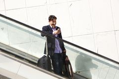Handsome mature business man on escalator using mobile phone. Portrait of handsome mature business man on escalator using mobile phone Royalty Free Stock Photography