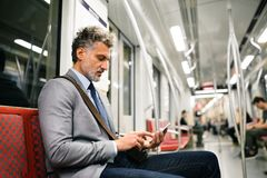 Mature businessman with smartphone in a metro train. Handsome mature businessman in a city. Man with smartphone travelling by subway train Stock Photos
