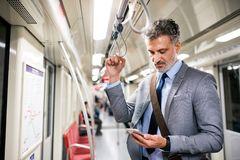 Mature businessman with smartphone in a metro train. Handsome mature businessman in a city. Man with smartphone travelling by subway train Royalty Free Stock Images