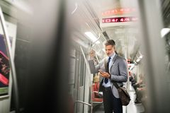 Mature businessman with smartphone in a metro train. Handsome mature businessman in a city. Man with smartphone travelling by subway train Stock Photo