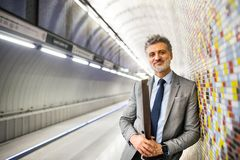 Mature businessman waiting on a metro station. Handsome mature businessman in a city. Man waiting for the train at the subway station Royalty Free Stock Photo