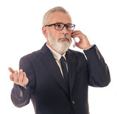 Handsome mature businessman with gadget. Handsome bearded mature businessman in classic suit and eyeglasses is talking on the mobile phone, isolated on white royalty free stock photos