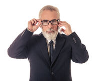 Handsome mature businessman with gadget. Handsome bearded mature businessman in classic suit and eyeglasses is talking on the mobile phone and looking at camera stock image