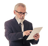 Handsome mature businessman with gadget. Handsome bearded mature businessman in classic suit and eyeglasses is using a digital tablet, on a white background royalty free stock photos