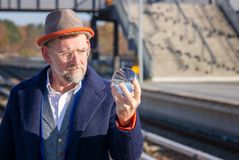 Mature businessman looking at glass sphere at train station stock images