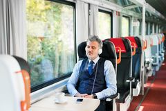 Mature businessman with smartphone travelling by train. Handsome mature businessman travelling by train. A man with smartphone and headphones, listening to Royalty Free Stock Photo