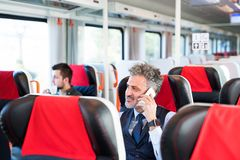 Mature businessman with smartphone travelling by train. Handsome mature businessman travelling by train. A men with smartphone, making a phone call Stock Photos