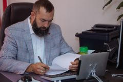 Handsome mature businessmen working with documents at office. Handsome mature bearded businessmen sitting at the table and working with documents at office Royalty Free Stock Images