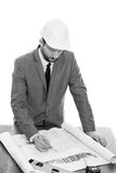 Handsome mature contractor drawing a building plan. Architect working. Black and white studio portrait of a professional male engineer wearing protective helmet Stock Images