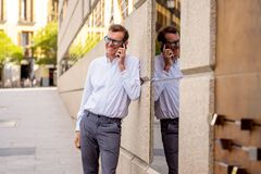 Handsome mature creative freelance businessman talking on mobile phone and smiling leaning on modern background outdoor urban area royalty free stock photography