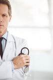 Handsome mature doctor. Cropped image of handsome mature doctor holding a stethoscope and looking at camera while standing with folded arms Stock Photos