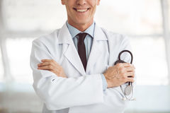 Handsome mature doctor. Cropped image of handsome mature doctor holding a stethoscope and smiling while standing with folded arms Stock Photo