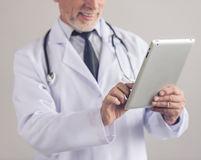 Handsome mature doctor. Cropped image of handsome mature medical doctor in white coat using a digital tablet and smiling, on gray background Stock Photos