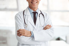 Handsome mature doctor. Cropped image of handsome mature doctor smiling while standing with folded arms Royalty Free Stock Photography