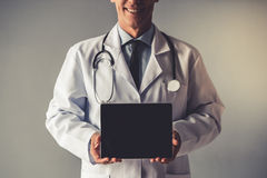 Handsome mature doctor. Cropped image of handsome mature doctor in white coat holding a digital tablet, on gray background Royalty Free Stock Photos