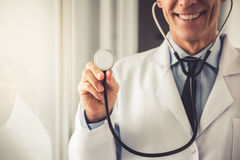 Handsome mature doctor. Cropped image of handsome mature doctor in white coat holding a stethoscope and smiling while standing in hospital corridor Stock Images
