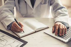 Handsome mature doctor. Cropped image of handsome mature doctor in white coat making notes while working in his office Royalty Free Stock Images