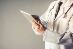 Handsome mature doctor. Cropped image of handsome mature doctor in white coat using a digital tablet, on gray background Stock Image