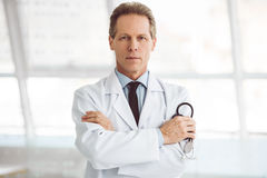 Handsome mature doctor. Is holding a stethoscope and looking at camera while standing with folded arms Stock Images