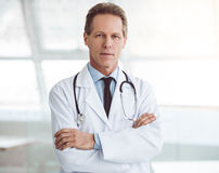 Handsome mature doctor. Is looking at camera while standing with folded arms Stock Photo